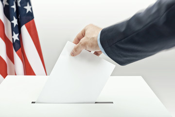Caucasian male in suit holding ballot paper in hand and throwing it into election box with US flag on background