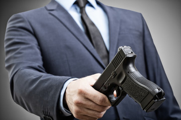 White man holding handgun in hand and trying to pass it to someone