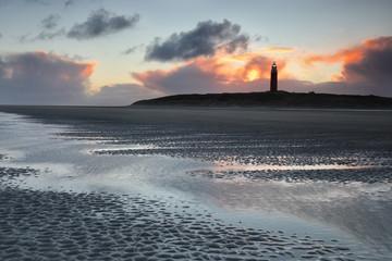 sunrise behind lighthouse on Dutch island