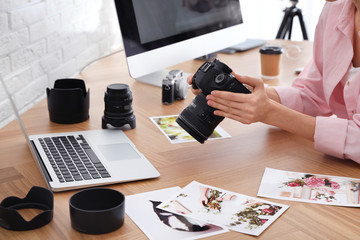 Professional photographer with camera working at table in office, closeup Fotobehang