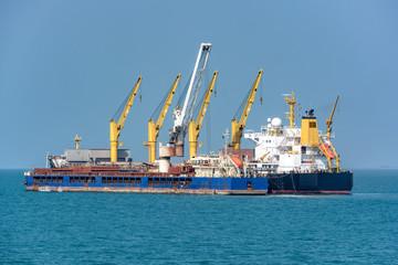 Loading ocean-going bulk carrier ship with Bauxite aluminum ore from the mini bulk carrier (feeder)...