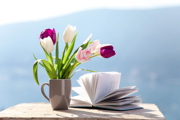 Fotomurales - Tulips and opened book at wooden table outdoors. Spring still life at sea beach. Blooming flowers on balcony at blue background of mountains. Pink, white, purple bouquet. Copy space.