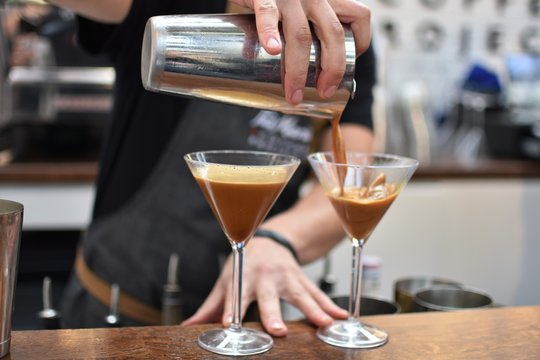 Midsection Of Bartender Pouring Cocktail In Martini Glass