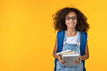 Cheerful young african girl kid in eyeglasses holding notebook and books for study isolated over yellow background