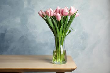 Spoed Fotobehang Tulp Beautiful pink spring tulips in vase on wooden table