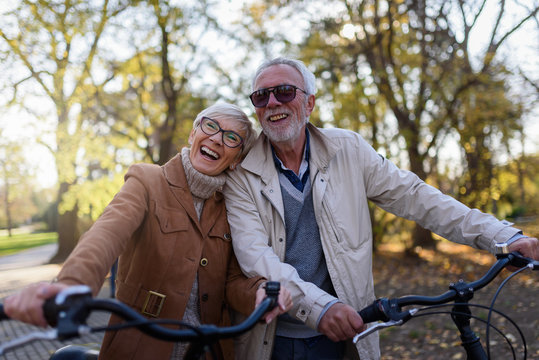 Cheerful active senior couple with bicycle in public park together having fun. Perfect activities for elderly people.