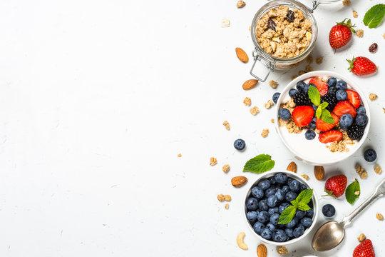 Greek yogurt granola with fresh berries on white table.