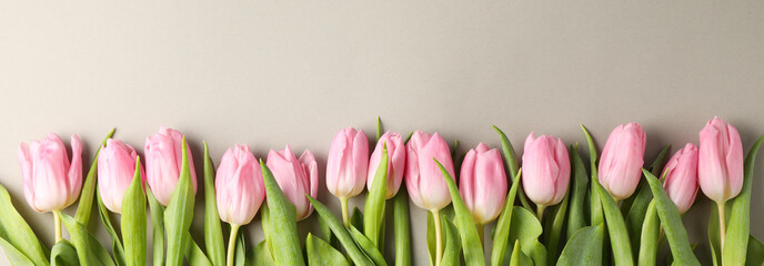 Pink tulips on grey craft background, top view and space for text