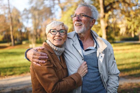 Smiling senior couple walking in the park together enjoying retirement