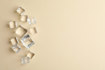 Crystal clear ice cubes on beige background, flat lay. Space for text