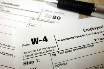 Blank W-4 form and a pen. Tax season