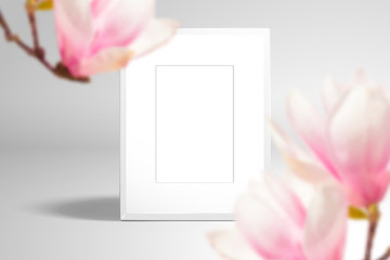 Empty white photo frame or picture frame. In the foreground are large magnolia flowers. Realistic template for spring romantic design