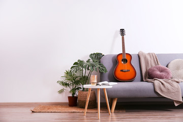 Minimalistic interior design concept. Acoustic guitar on grey textile sofa in spacious room of loft style apartment with wood textured laminated flooring. Background, copy space, close up. Wall mural