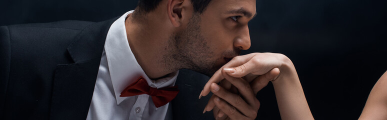 Panoramic shot of handsome man kissing hand of woman isolated on black