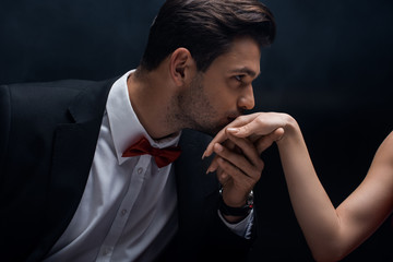 Handsome man in suit kissing hand of woman isolated on black