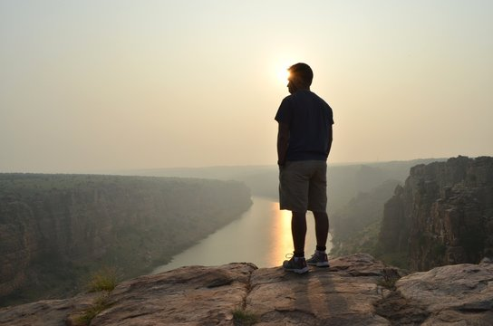 Rear View Of Man Standing On Cliff Above River At Sunset