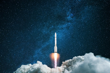 Rocket starts in the night starry sky. A spaceship flies into outer space. Concept of travel to...