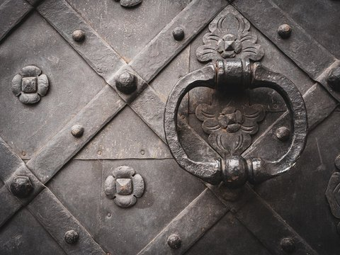 Closeup shot of an ancient door in black with metal handle