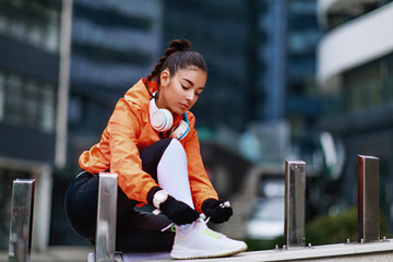 Door stickers Jogging Young woman in an orange hoodie ready for jogging in the city