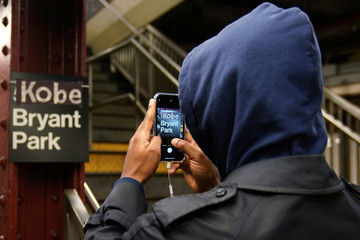 "A man takes a picture of a New York City subway sign that has been changed to read ""Kobe Bryant Park"" in reference to the deceased NBA player in the Manhattan borough of New York City"