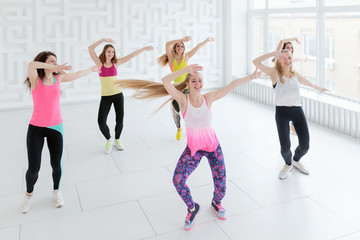 Young women in sportswear dancing with hands raised up at dance fitness class. High angle view