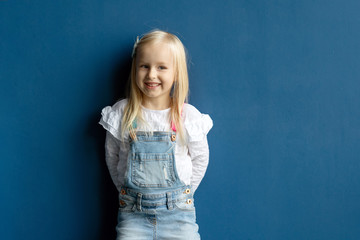 Happy toddler pretty girl with blond hair smiling while posing on blue wall background