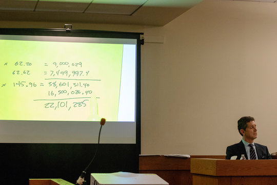 A projection of a post-it note shows calculations regarding the sale of stock options made by Alex Gorsky, chairman and CEO of Johnson & Johnson, as Gorsky takes the stand in New Jersey Supreme Court in New Brunswick