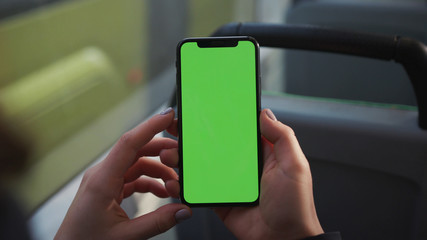 Lviv, Ukraine - May 19, 2018: Hands use touch holding a mobile telephone with a vertical green screen in tram chroma key smartphone technology cell phone street touch message display hand