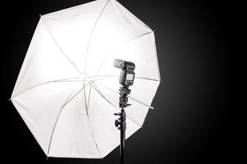 Studio stand with speedlight photo flash and white umbrella reflector