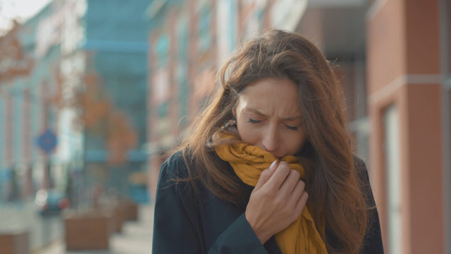Face young woman stand sneezing coughs feel sick at outdoor fever cold allergy city beautiful disease female nose lady runny tissue air pollution adult illness district slow motion