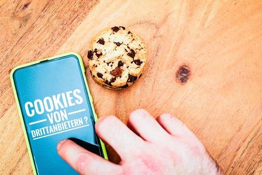 Cookies mit einem Tablet zur Verdeutlichung von Cookie Bannern für Websites mit auf deutsch Cookies von Drittanbietern? in English Third party cookies