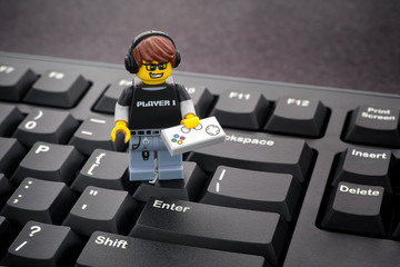 Tambov, Russian Federation - January 24, 2020 Lego Video Game Guy minifigure with gamepad standing on a black computer keyboard.