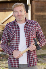 mature happy caucasian man holding an axe