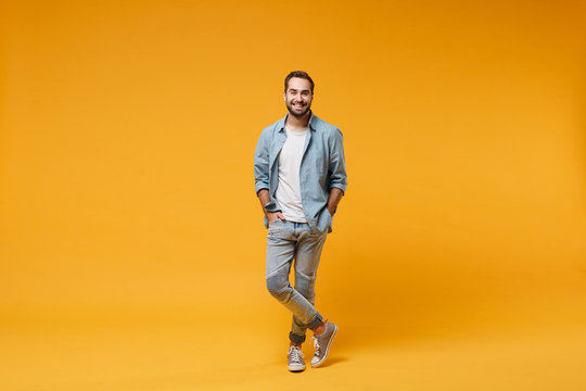 Smiling young bearded man in casual blue shirt posing isolated on yellow orange background, studio portrait. People sincere emotions lifestyle concept. Mock up copy space. Holding hands in pockets.
