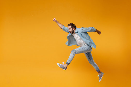 Cheerful young bearded man in casual blue shirt posing isolated on yellow orange background studio portrait. People lifestyle concept. Mock up copy space. Jumping with outstretched hand like Superman.