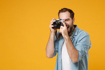 Cheerful young man in casual blue shirt posing isolated on yellow orange background, studio portrait. People sincere emotions lifestyle concept. Mock up copy space. Hold retro vintage photo camera.