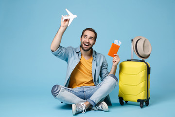 Funny traveler tourist man in yellow clothes isolated on blue background. Passenger traveling abroad on weekend. Air flight journey Sit near suitcase hold passport boarding pass tickets air plane.