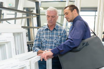 salesman with worker in double glazing premises