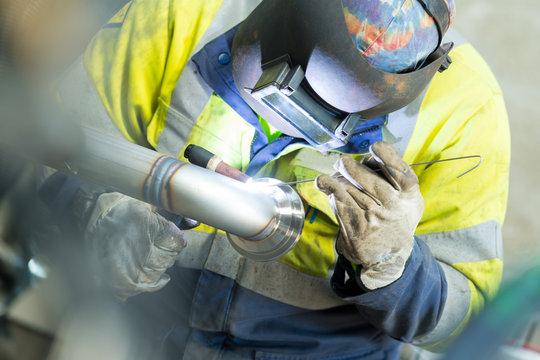 welding man welding pipe in industry