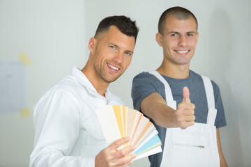 painter giving ok sign holding color swatch