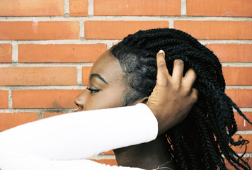 Close-Up Of Woman With Cornrow Braids Against Brick Wall