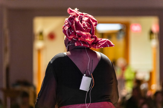 Rear view of woman wearing red turban while standing and giving speech on stage. in front of audience at auditorium hall with mike holder on back