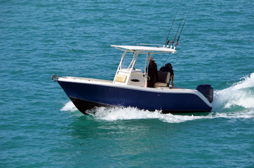 Two fishermen aboard aa small blue and white sport fishing boat powered by a single outboard engine slowly cruising on the Florida Intra-Coastal Waterway