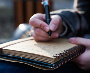 Close-Up Of Hand Writing In Diary