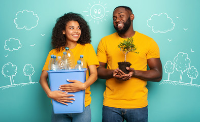 Happy couple hold a plastic container with bottles and a small tree over a light blue color. Concept of ecology, conservation, recycling and sustainability