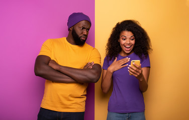 Girl receive a lot of hearths on social and boy is jealous about it. Yellow and violet background