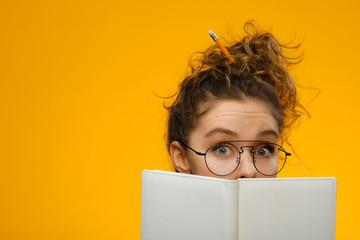 Closeup portrait of teenager hiding behind notebook