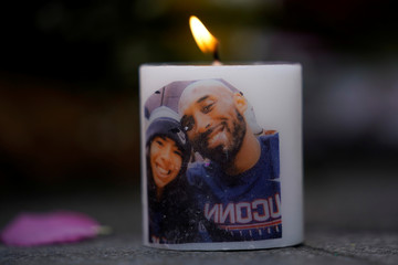 NBA basketball star Kobe Bryant and his daughter Gianna's image are shown on a burning candle as fans pay their respects at a memorial outside the Staples Center at L.A. Live in Los Angeles