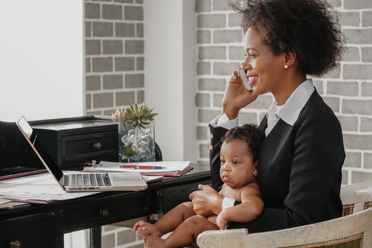 african american business woman with baby working at home