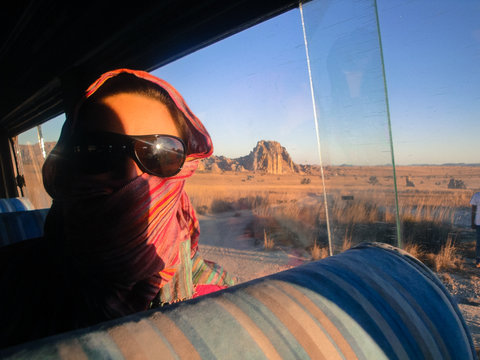 Portrait Of Woman Wearing Sunglasses And Scarf While Sitting In Bus